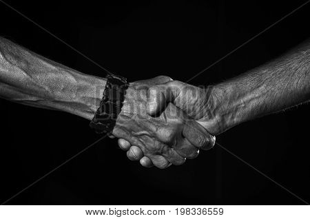 A firm handshake of two men in black and white.