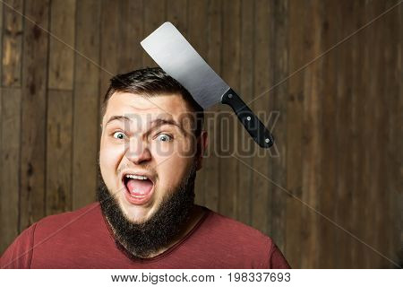 brutal thick man with a sharp knife in his head against the background of a wooden wall