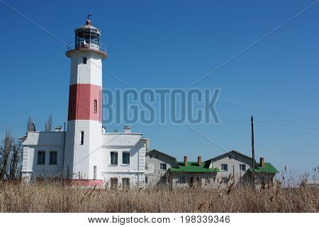 Old lighthouse against the blue sky. Red and White Lighthouse. Surface level of lighthouse on field against sky.