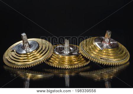 Watch Repair: Vintage Pocket Watch Fusee Cones Resting on a Black Surface