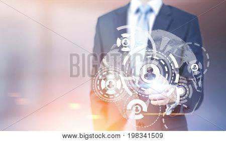 Unrecognizable businessman interacting with a round network and HUD sketch in front of the Earth in a blurred office. Toned image mock up double exposure.
