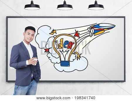 Portrait of a smiling Asian visioner wearing a suit with jeans and holding a coffee to go. He is standing near a whiteboard with a colorful startup idea sketch