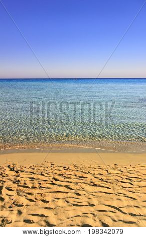 Summer seascape, Apulia coast: Marina di Pulsano beach.It's characterized by a alternation of sandy coves and jagged cliffs overlooking a truly clear and crystalline sea.Lonely boat on the horizon.