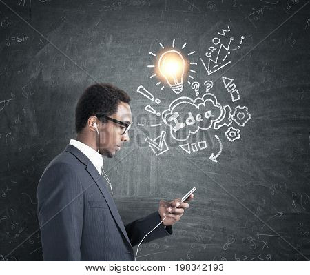 Side view of an African American businessman in a gray suit looking at his smartphone screen. He is wearing headphones. Blackboard background with an idea scheme on it.