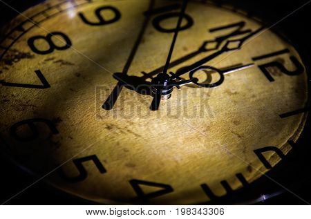 Clock, Watch. Old clock. Time watch. Very old and beautiful wall clock in shadow. Antique clock. Old watch with yellow color on it.