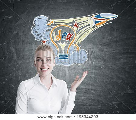 Portrait of a smiling blonde business coach pointing at a colorful startup idea sketch drawn on a blackboard behind her.