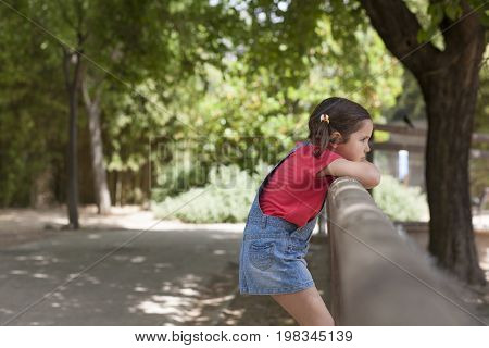 Angry and thoughtful little girl. Green park background