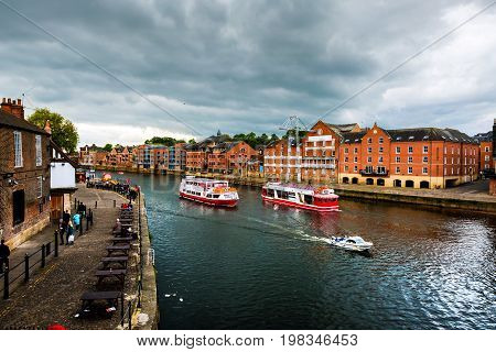 York, UK. Embankment area of Ouse river in York, UK. Heavy clouds and touristic boats