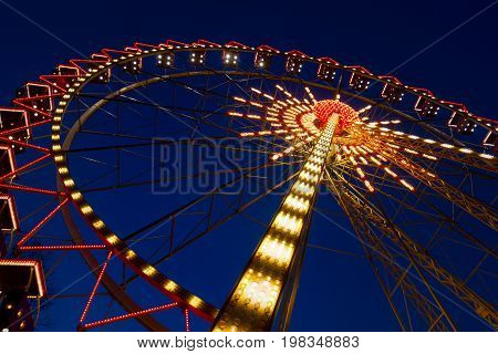 Ferris Wheel In The Evening. Cabins Of A Ferris Wheel Illuminated With Colored Lamps. Rides At City