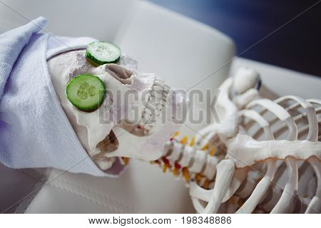 Skeleton In Spa Salon With Towel On Her Head And Mask On Her Face, Relaxes, Care Themselves. An Absu