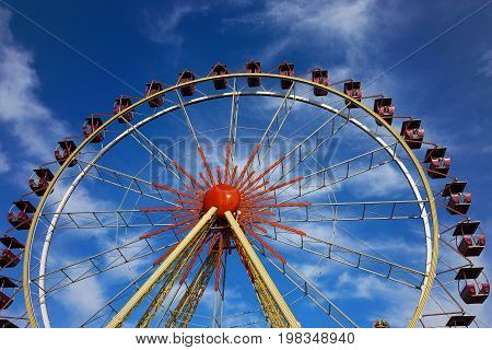 Ferris Wheel. Open Booths Of The Ferris Wheel At The Sky With Beautiful Clouds. Rides At City Park.