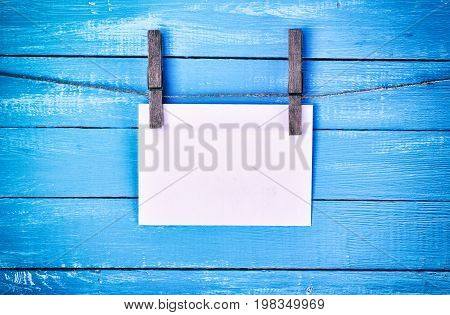 White paper envelope hanging on a rope buttoned with wooden old clothespins on a blue background