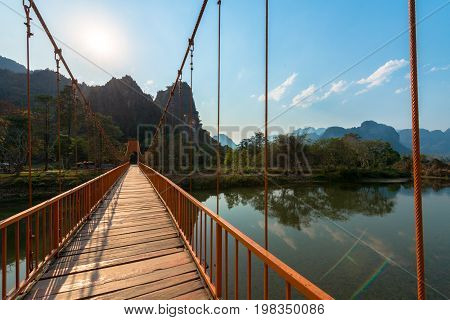 Picture of orange bridge over the Nam Song River with tropical vegetation. Close to Tham Chang Cave in the city of Vang Vieng Laos.