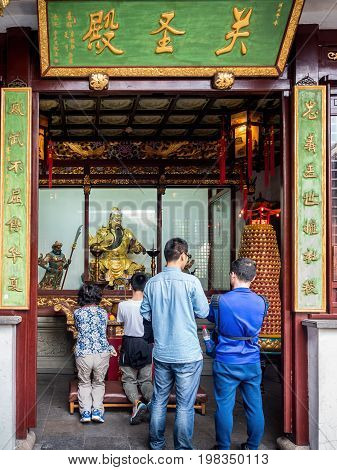 Shanghai, China - Nov 6, 2016: In the 600-year-old Old City God Temple. Patrons waiting in turn to offer their respect to General Guan Yu (patron Taoist deity), the statue in glass cabinet.