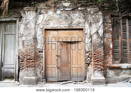Old wooden door and brick wall covered with wood roots in Semarang, Indonesia