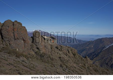 Derelict mountain hut, Refugio Alemana, in the mountainous landscape of Parque Yerba Loca set in a glacial valley close to Santiago, capital of Chile. Santiago in the distance under a layer of smog.