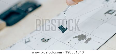 Technician With Tweezers Carries Parts Of Mobile Phone During Service