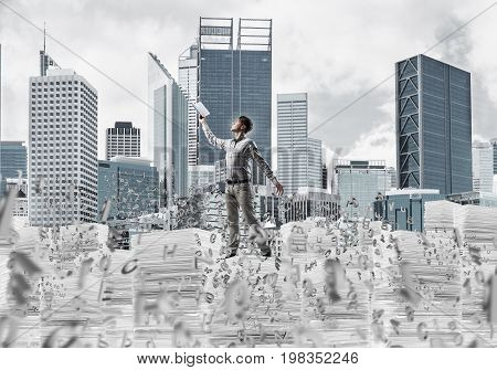 Man in casual wear keeping hand with book up while standing among flying letters with cityscape on background. Mixed media.