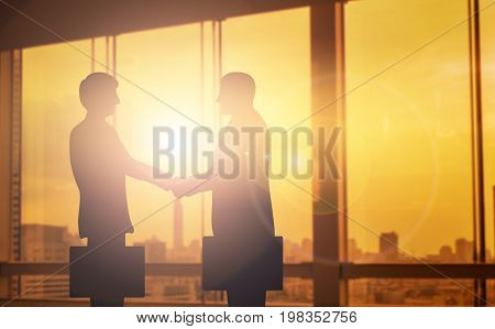 silhouettes two businessmen handshake in cooperation agreement concept at office and successful business partner. business man shaking hands to seal a deal with his partner