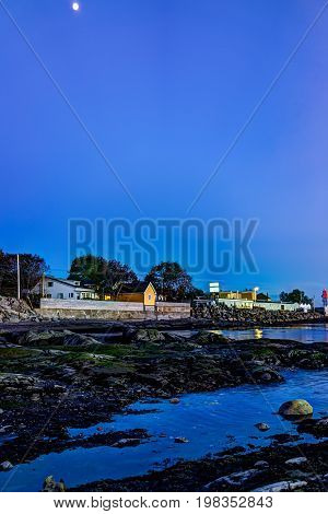 Rimouski Canada - June 4 2017: Blue twilight in Gaspesie region of Quebec by Saint Lawrence river with rock boulders in shallow water and seaweed with Motel sign