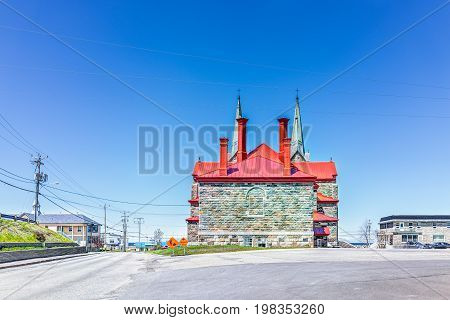 Sainte-Anne-des-Monts Canada - June 5 2017: Back of red painted stone church in Gaspesie Quebec region city