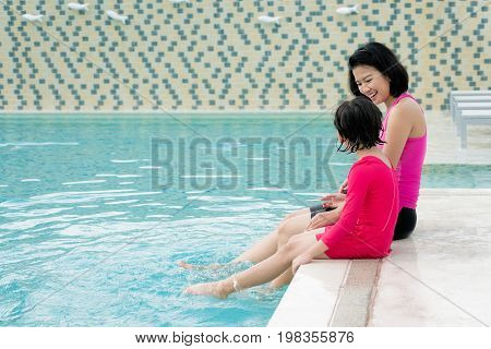 Happy Asian family mother and daughter in hotel swimming pool enjoying summer vacation. Asian family concept.
