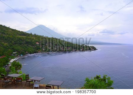 Bali, Indonesia - July 2017. View to the Amed beach and volcano from the cliff