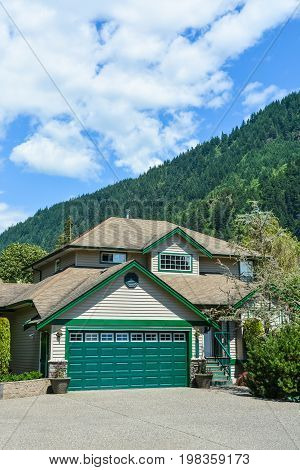 Big family house with wide concrete driveway and green double wide garage door. Residential house with mountain and blue sky background