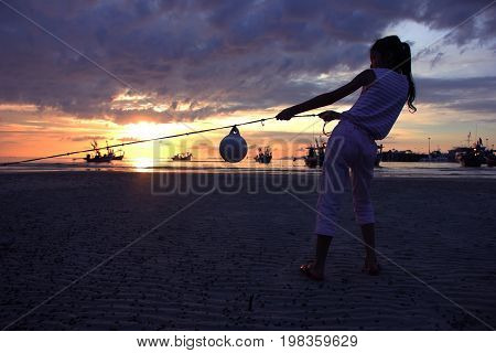 Asian girl pulling rope and mooring buoy on the beach at sunset.