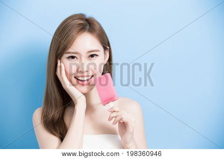 woman take popsicle and touch her face on the blue background