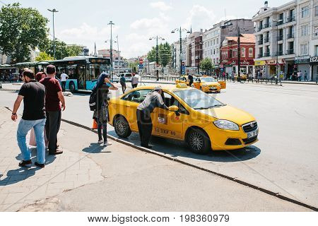 Istanbul, June 11, 2017: A traditional yellow taxi on the street in the Fatih district of Istanbul, Turkey. Customers are next to the car. Urban life style. Transportation of passengers. A business.
