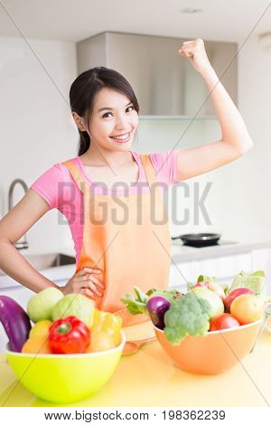 beauty housewife show fist and smile in the kitchen