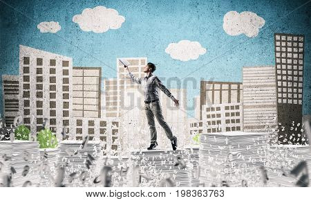 Man in casual wear keeping hand with book up while standing among flying letters with drawn cityscape on background. Mixed media.
