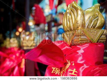 Shanghai, China - Nov 6, 2016: In the 600-year-old Old City God Temple. A decorative wooden object painted in gold on railing post. The post is wrapped with a red ceremonial ribbon. Low-light.