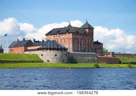 Medieval fortress of Hameenlinna on the shore of Vanajavesi lake on a July day. Finland