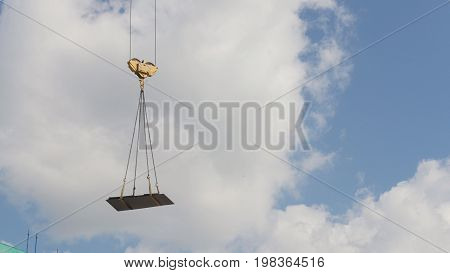 A crane lifting heavy equipments on a construction site - telephoto view in front of blue sky