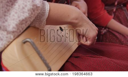 Gusli - woman in Russian folk costume playing vintage musical instrument , close up