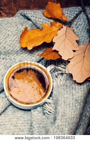 Red and Orange Autumn Leaves Background with coffee cup. Yellow Fallen autumn leaves on vintage wooden old backdrop