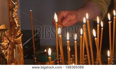 The parishioner put a candle inside an Orthodox church, close up