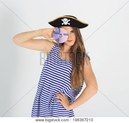 Nice young woman with pirate cd or  disk and hat with skull and crossbones. Concept of software piracy and copyrighting