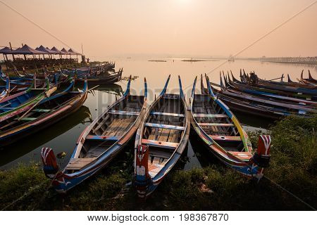 Sunrise at U Bein Bridge with boat Mandalay Myanmar.
