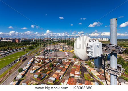 Telecommunication equipment with microwave antennas of mobile operator against blue sky with clouds and city