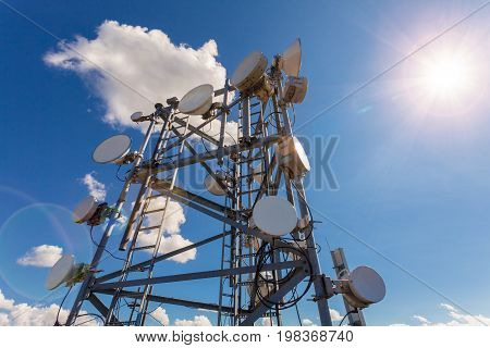 Telecommunication tower with TV antennas satellite dish microwave and panel antennas of mobile operator against blue sky and sun