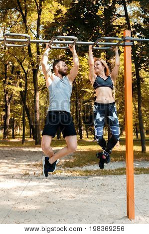 Young sportive girl and bearded man doing pull-ups exercises on crossbar in a parrk at autumn day. Comcept of healthy lifestyle.