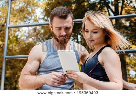 Young athletic girl and bearded man browsing the internet on a white tablet PC while doing fitness exercises in park at sunny autumn day.