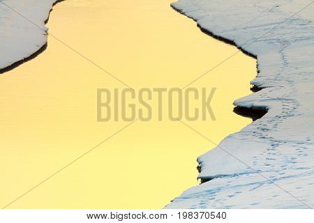 Sunlight reflection on smooth water surface on stream in winter aura.