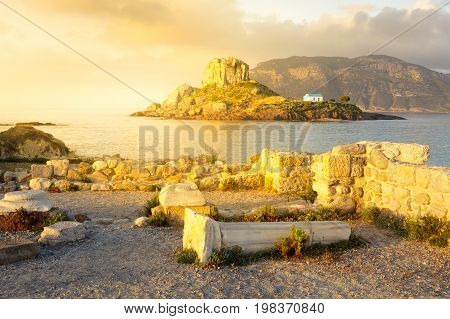 Ancient ruins and small island Kastri with traditional orthodox church in Kefalos bay in Kos island Greece.