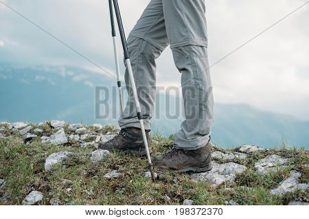 Female hiker with trekking poles walking in the rocky mountains view of legs.