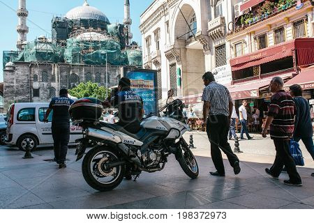 Editorial image of two Fatih district police officers on duty and random curious passerby are wondering what is going on, event took place in Istanbul, Turkey on June 15, 2017.