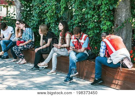 Editorial image of two Turkish turism police officers looking at their phones at Sultanahmet square, with group of people sitting nearby.